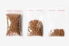 套与在白色隔绝的优质碎荞麦片的三个空,半和充分的塑料透明拉链袋子 真空包装m 免版税库存图片
