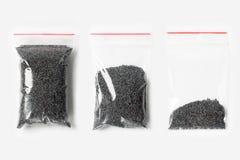 套与在白色隔绝的罂粟种子的三个空,半和充分的塑料透明拉链袋子 与稀土的真空包装大模型 免版税图库摄影