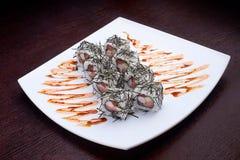 套与螃蟹和甜调味汁的寿司maki在白色板材 在背景的日本食物 库存照片