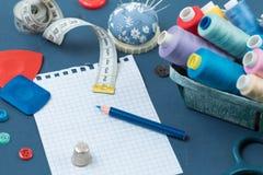 套与螺纹的多彩多姿的卷缝合的,是织品的白垩,缝合的辅助部件和一片叶子纪录的在蓝色后面 库存照片
