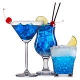 套与装饰的蓝色鸡尾酒从在白色背景和五颜六色的秸杆隔绝的果子 库存图片