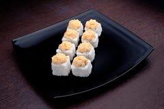 套与金枪鱼的寿司maki在黑色的盘子 在背景的日本食物 库存照片