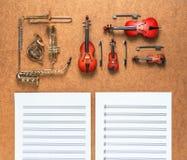 套五金黄铜管乐器和四串起乐队乐器和说谎在它附近的活页乐谱 概念电吉他例证音乐 免版税库存照片