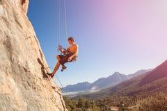 套住绳索的男性攀岩运动员 免版税图库摄影