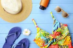 套使季节泳装靠岸的妇女` s五颜六色的辅助部件,太阳镜、触发器、遮光剂和帽子有赤素馨花的开花上面 免版税库存照片
