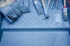 套刷子和蓝色油漆在油漆盘子 免版税图库摄影