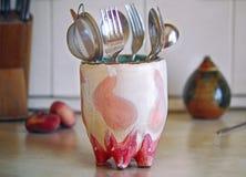 套厨房工具在桌上的一个滑稽的陶瓷杯子站立 免版税图库摄影