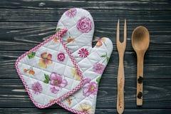 套厨房纺织品、器物和一个罐在深灰木背景 库存照片