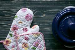 套厨房纺织品、器物和一个罐在深灰木背景 免版税库存照片
