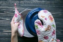 套厨房纺织品、器物和一个罐在深灰木背景 图库摄影