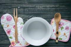 套厨房纺织品、器物和一个罐在深灰木背景 免版税库存图片