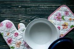 套厨房纺织品、器物和一个罐在深灰木背景 库存图片