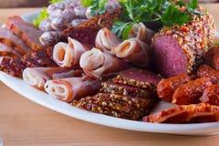 套另外开胃菜,象jamon、烟肉和蒜味咸腊肠在一块大板材 图库摄影