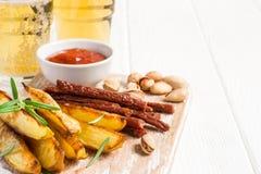 套啤酒的不同的开胃菜在一个切板和玻璃供食用啤酒 库存图片