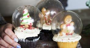 套圣诞节杯形蛋糕雪地球 库存图片