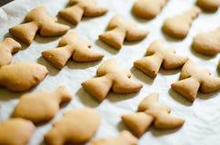 套圣诞节题材塑造了在白色烹调纸背景的曲奇饼 Ange、雪人和鱼 库存照片