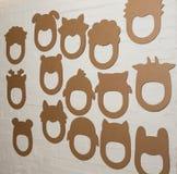 套在一个白色砖墙上的纸板面具 免版税库存图片