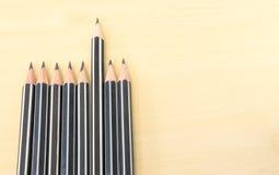套在一条线的黑铅笔与一个卓著 免版税库存图片