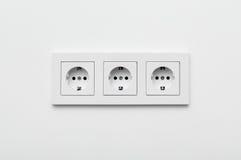 套在墙壁上的三个插口 图库摄影