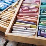 套在开放木艺术家箱子的多彩多姿的淡色蜡笔 免版税图库摄影