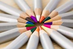套在木书桌上的不同的色的铅笔 免版税库存图片