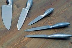 套在木桌上的五把钢厨刀 库存图片