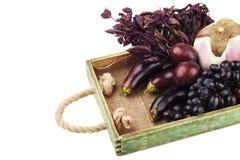 套在木盘子的不同的紫罗兰色未加工的蔬菜 免版税库存照片