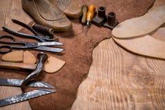 套在木背景的皮革工艺工具 鞋匠的工作场所 免版税库存图片