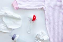 套在桌上的新出生的供应:尿布,装豆子小布袋,瓶,衣服 免版税库存图片