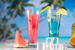 套在海滩的异乎寻常的饮料有蓝色海洋背景 免版税库存照片