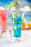 套在海滩的异乎寻常的饮料有蓝色海洋背景 免版税库存图片