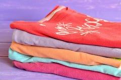 套在淡紫色木背景的五颜六色的儿童衣物 堆女孩的时髦的明亮的棉花女衬衫 宏指令 库存图片