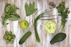 套在白色的绿色菜绘了木背景:撇蓝,鲕梨,抱子甘蓝,苹果,黄瓜,葱,豌豆 免版税图库摄影