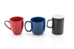 套在白色的黑,红色和蓝色杯子 免版税图库摄影