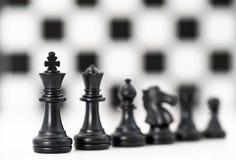 套在白色背景的黑棋子 免版税库存照片