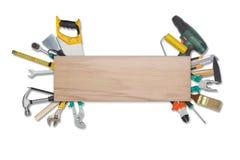 套在白色背景plankisolated的木后的建筑工具 锯,玻璃,卷尺,板钳 库存图片