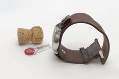 套在皮带、香槟黄柏和塑料fl的人手表 库存照片