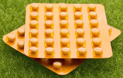 套在草背景的橙色药片天线罩包装 免版税图库摄影