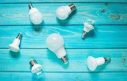 套在蓝色木背景的不同的行LED电灯泡 库存图片