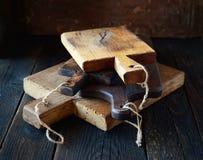 套在黑暗的背景的不同的老木砧板 库存图片