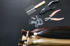 套在黑暗的背景的sevral颜色头发引伸工具 免版税库存照片