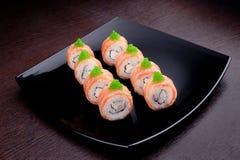 套在黑色的盘子的寿司maki费城 在背景的日本食物 免版税库存照片
