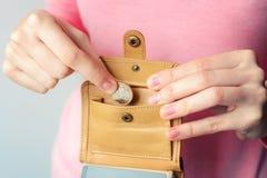 套头衫的一名妇女在一个棕色钱包投入一枚欧洲硬币 库存照片