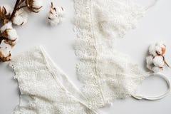 套女用贴身内衣裤,米黄与黑白色丝带 在用棉花装饰的白色背景的白色背景开花 图库摄影