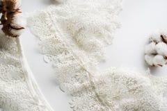 套女用贴身内衣裤,米黄与黑白色丝带 在用棉花装饰的白色背景的白色背景开花 库存图片
