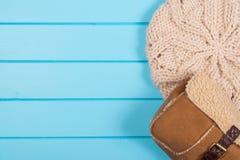套妇女的被编织的贝雷帽和冬天袋子在一木backgroun 库存图片