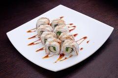 套寿司在白色板材的maki龙 在背景的日本食物 免版税库存图片
