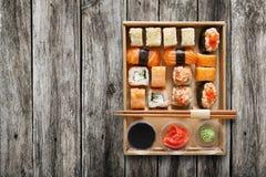 套寿司maki和卷在箱子在木头 免版税库存照片
