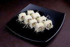 套寿司maki用在黑色的盘子的乳酪 在背景的日本食物 免版税库存照片
