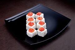 套寿司maki用在黑色的盘子的鱼子酱 在背景的日本食物 免版税图库摄影